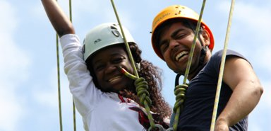 Students celebrate a successful climb at the Ivey Spencer Ropes Course in London, Ontario.